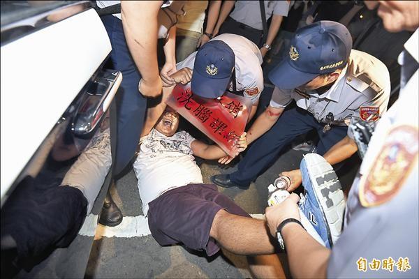 「捍衛教育中學陣線」昨晚夜襲教育部噴漆,抗議教育部不撤銷違法的黑箱課綱,抗議學生隨即遭警方抬離。(記者簡榮豐攝)