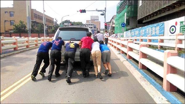 嘉市消防隊員、役男加上陳姓男童等人,聯手將車子推上坡解危(記者王善嬿翻攝)