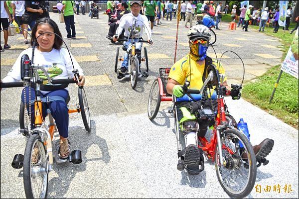 輪椅族朋友騎手搖式自行車暢遊橋頭。(記者蘇福男攝)