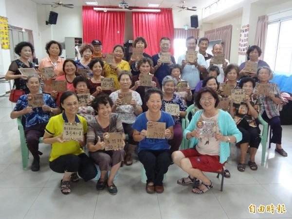 西港港東里民高興展示自己的陶製金獅門牌。(記者楊金城攝)
