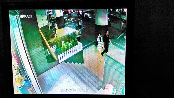 監視器拍下兩人牽手離開捷運站,狀似親密。(記者王冠仁翻攝)