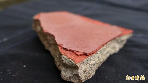 國定古蹟紅毛城進行修繕工程,圖為由外牆剝落下的石塊。最外層為防水漆,下一層則是土硃灰壁,可以看到明顯的顏色差異。(記者李雅雯攝)