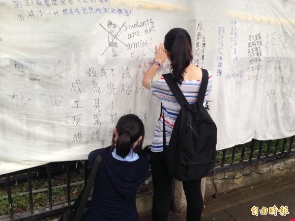 學生們用白布對抗拒馬,寫滿了反對黑箱課綱的心聲。(記者林曉雲攝)