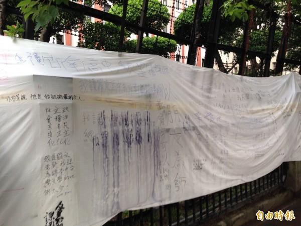 中學生在教育部外牆圍上白布,即使突然下了一陣大雨,使上面的字模糊了,卻燒不熄學生的反黑箱課綱怒火。(記者林曉雲攝)