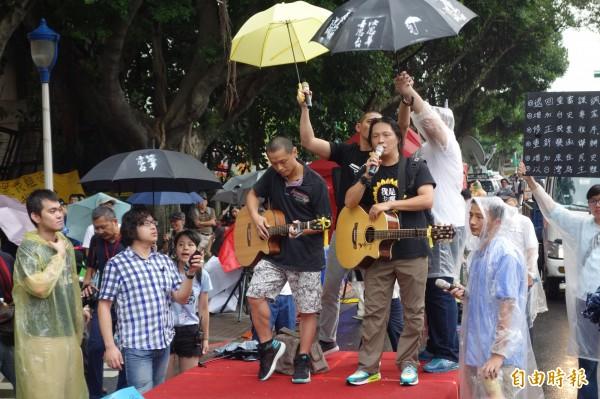 成淵高中英文老師羅逸楓(右拿吉他者)、清水高中數學老師江逢維(左拿吉他者)在風雨中聲援中學生,高唱廣東歌曲「海闊天空」鼓勵。(記者吳柏軒攝)
