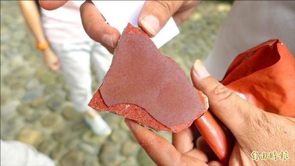 國定古蹟紅毛城進行修繕工程,圖為從外牆剝落下的石塊,最外層為防水漆,下一層則是土硃灰壁,可以看到明顯的顏色差異。(記者李雅雯攝)