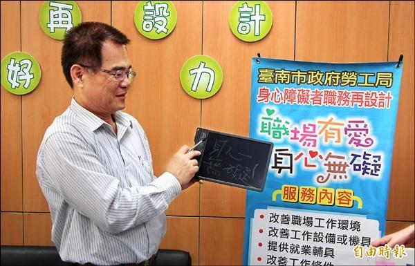 南市勞工局長王鑫基示範職務再設計相關輔具,呼籲身障朋友與雇主多申請,職場工作更順利。(記者王涵平攝)