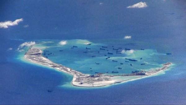 菲律賓就南海主權爭議要求國際仲裁,我國欲前往旁聽,卻遭國際法庭以「一中」因素拒絕。圖為中國在南海填海造陸,美濟礁周圍海域可見中國挖泥船。(路透檔案照)