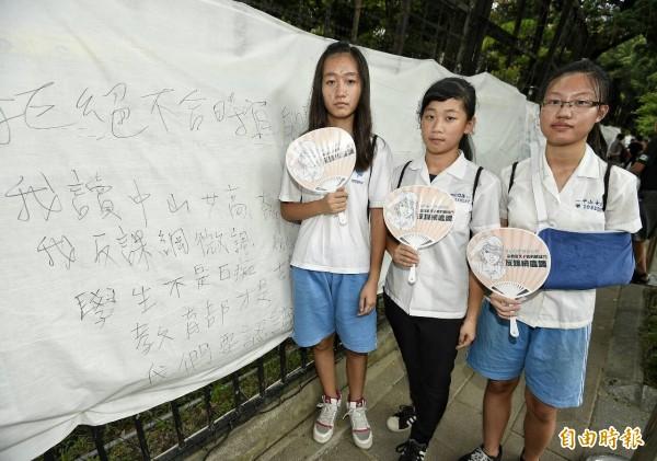 中山女高學生在教育部外牆的白布上寫出訴求。(記者陳志曲攝)