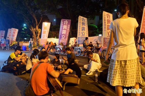 不滿高中課綱微調,反課綱學生團體22日下午號召包圍教育部,現場聚集近300人,晚間活動持續進行,參加民眾席地而坐。(記者王藝菘攝)