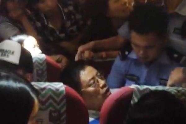 中國西部航空一名男乘客,因不滿氣候影響班機延誤,出手毆打空姐出氣。圖為警方上機欲將該乘客帶回調查。(圖擷取自微博影片)