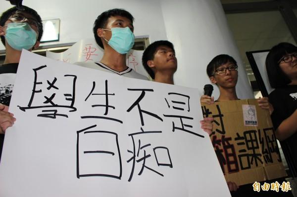 反課網學生持「學生不是白癡」的牌子,要求教育部撤回課綱。(記者張聰秋攝)