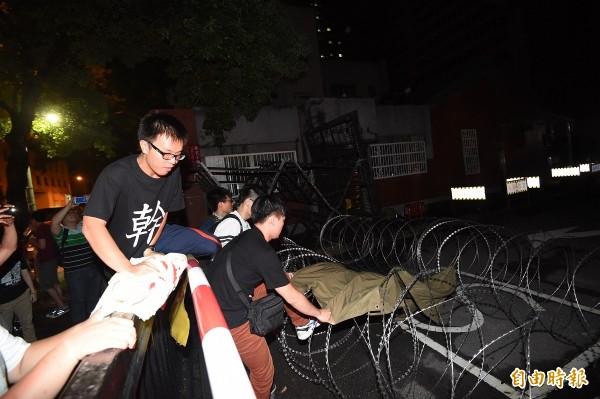 廖振輝拍攝反課綱中學生用厚布翻越側門拒馬,但僅傳出一張照片即遭到警方帶走,目前下落不明。(記者廖振輝攝)