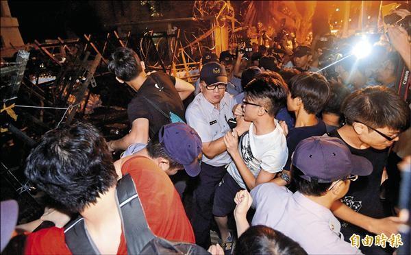 反課綱學生前天深夜衝進教育部,當時有民眾試圖進入教育部尋找被捕的學生,一度與警方發生推擠,現場媒體記者與攝影機也擠在人群中。(記者王敏為攝)
