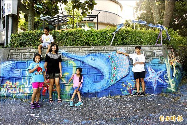 成功鎮廿五名學童發揮巧思,利用廢棄物將圖書館四周打造成海底世界創作牆。(記者王秀亭攝)