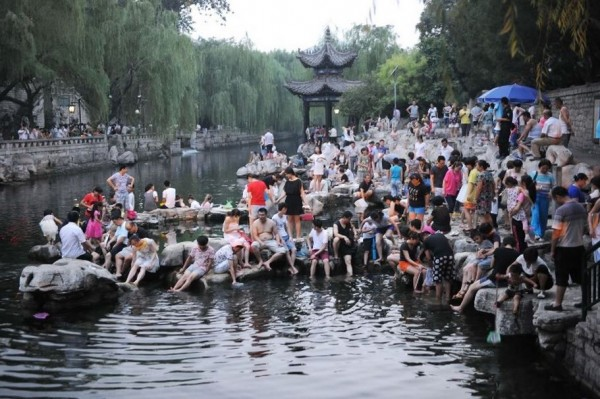 中國濟南一處護城河泉池,竟成為百名遊客的泡腳池,並經勸導後仍我行我素。(圖擷取自中評網)