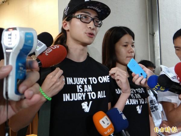 朱震將學生現在的態度「殺我一人即滅我全族」英文字樣T恤穿上身。(記者徐聖倫攝)