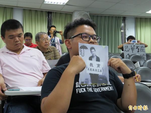 劉勇廷手持瓦楞紙版,上面貼有自殺學生林冠華的黑白照片,也寫著教育不是政治工具。(記者王揚宇攝)