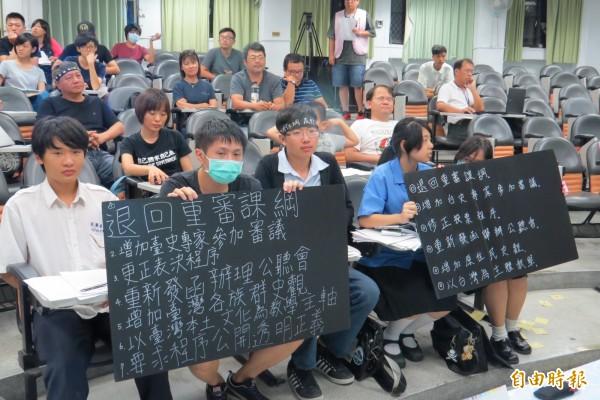 學生手持看板表達訴求。(記者王揚宇攝)