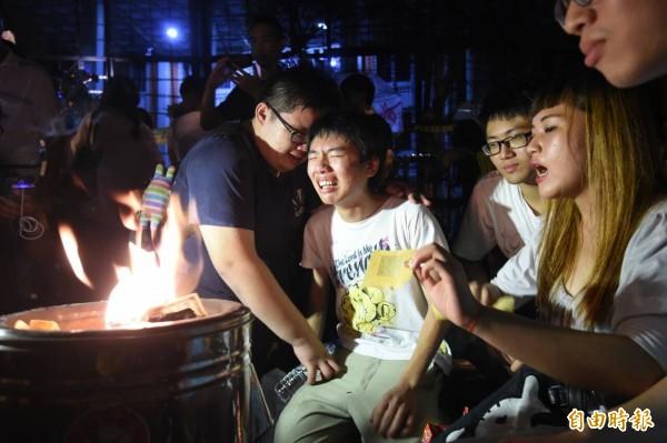 學生在現場點燃冥紙,並表示一定會陪冠華過完20歲生日。(記者劉信德攝)