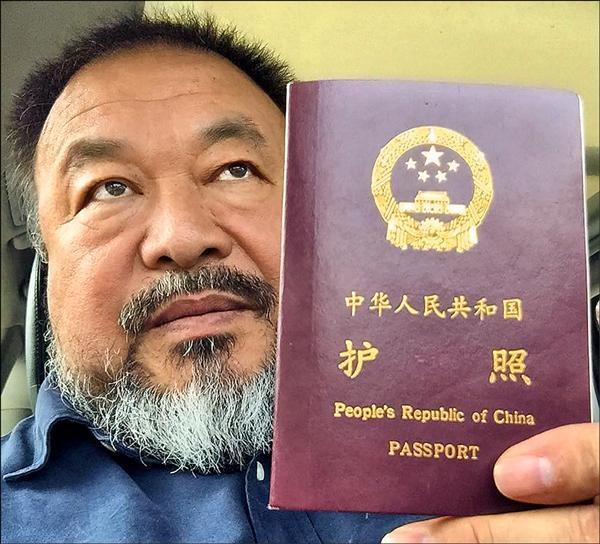 艾未未手持本月二十二日才獲發還的護照。(法新社)