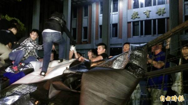 已經有20餘位民眾在凌晨1點40分攻入教育部,有民眾抬出路障墊在拒馬上,供門外抗議民眾踩踏。(記者方賓照攝)