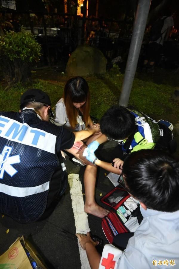 一名女子腿部受傷,救護人員立刻給予協助。(記者劉信德攝)