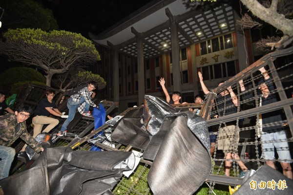 得不到教育部長吳思華出來回應,學生及民眾在今天凌晨1點33分,徒手推倒教育部內的高聳拒馬,翻入教育部的前庭。(記者方賓照攝)