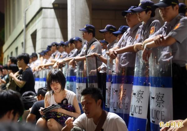 反黑箱課綱的學生與民眾占領教育部前庭後席地而坐,與警方對峙。(記者方賓照攝)