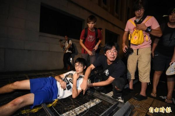一名民眾在進入教育部時不慎跌落拒馬,手臂輕微刮傷。(記者劉信德攝)
