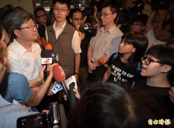 教育部長吳思華(左)30日在自殺學生林冠華所住社區召開記者會進行說明後,在離開時遭到反課綱學生包圍。(記者王敏為攝)