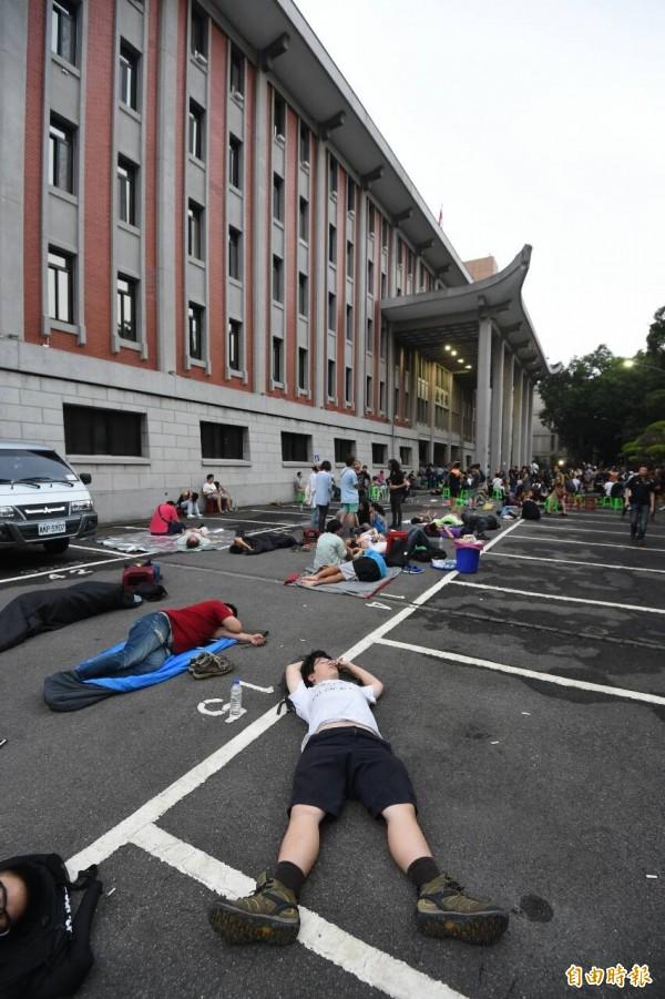今天清晨學生累攤,直接睡在柏油路面上。(記者劉信德攝)