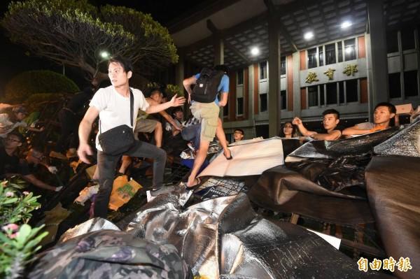 到凌晨1點半左右,抗議群眾開始翻越教育部外的拒馬蛇籠,並以障礙物跨過拒馬進入教育部前庭。(記者劉信德攝)