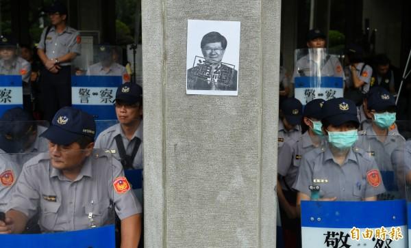 反黑箱課綱學生將通緝教育部長吳思華海報,貼在警方駐守的柱子上。(資料照,記者張嘉明攝)
