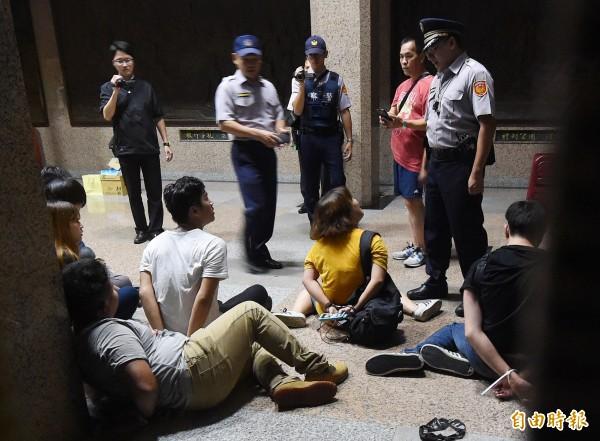 反黑箱課綱學生23日晚間夜襲教育部,衝入教育部大樓內,警方進入逮捕學生,反課綱微調北高發言人林冠華(左,穿白色T恤者)和其他學生被上手銬與束帶。(資料照,記者廖振輝攝)