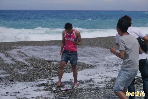遊客被突襲大浪追著跑,鞋子還差點被沖走,險象環生。(記者王峻祺攝)