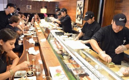 美國紐約市新規定:壽司的材料和生魚片必須事先進行冷凍。圖為7月在紐約高級壽司店內戴著手套製作壽司的師傅們。(圖片翻攝自共同社)