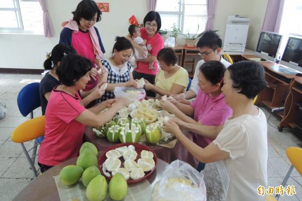 台南市樂齡學習示範中心志工們忙著剝落果文旦,將製作成果醬、清潔精等義賣。(記者劉婉君攝)