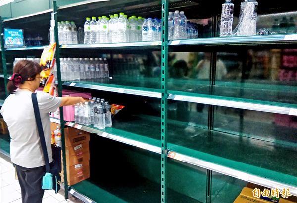 民眾將賣場貨架上瓶裝水幾乎搶購一空。(記者張嘉明攝)