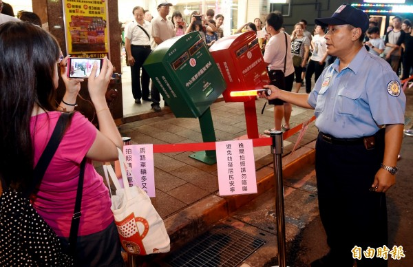 中華郵政決定暫時不移龍江路歪腰郵筒,12日晚間開始派保全守護 並維持民眾拍照秩序。(記者朱沛雄攝)