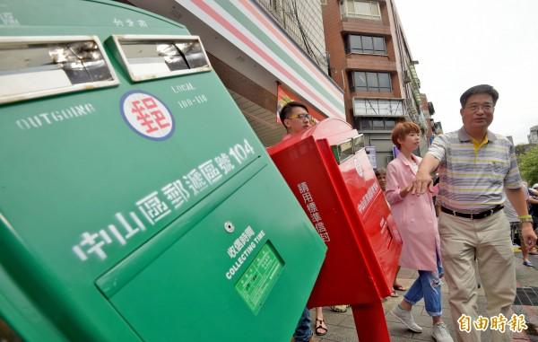 蘇迪勒颱風意外讓台灣多了一個觀光地標「歪腰郵筒」,吸引不少遊客特地前往拍照留念,受歡迎的程度甚至影響了台北南京龍江路口的交通,讓中華郵政宣布明天將替它們搬家(資料照,記者王敏為攝)