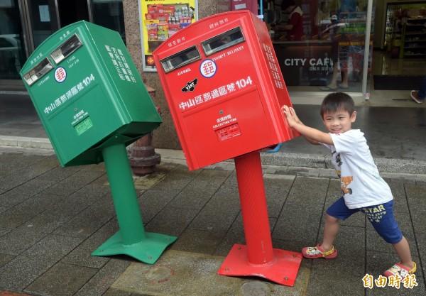 龍江路的郵筒遭掉蘇迪勒颱風吹下的招牌擊中,變形歪斜成了「歪腰」郵筒。(記者王敏為攝)