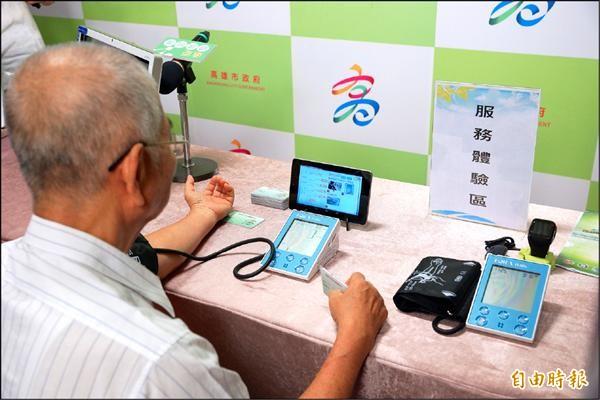 民眾用藍芽血壓機量測血壓,再透過平板電腦上傳資料。(記者方志賢攝)