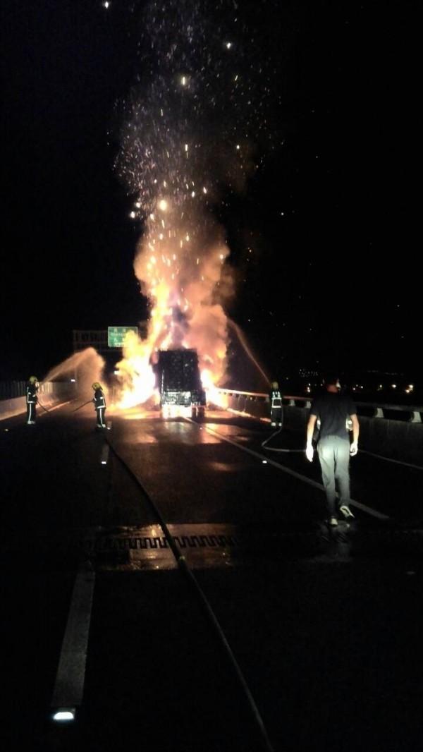滿載金紙的大卡車在國道三號麟洛段起火燃燒,消防人員趕到現場滅火(記者葉永騫翻攝)
