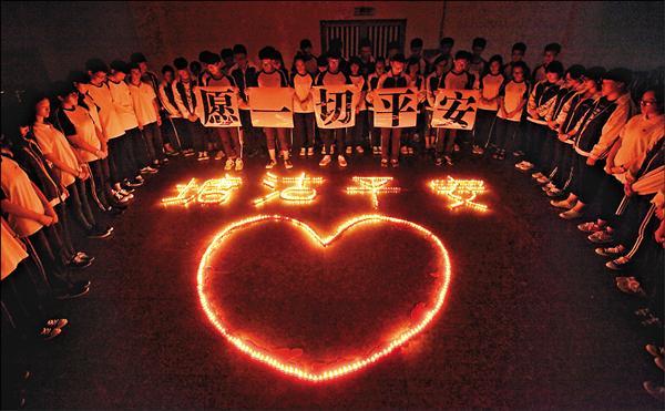 天津八一二大爆炸死傷慘重,浙江諸暨市一所學校的師生十三日晚間用蠟燭排起愛心與「塘沽平安」的字樣,希望一切平安。(路透)