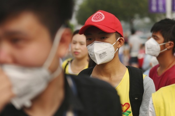 天津大爆炸後,因外界提醒空氣中恐含有有毒氣體,當地民眾紛紛戴上口罩。(法新社)