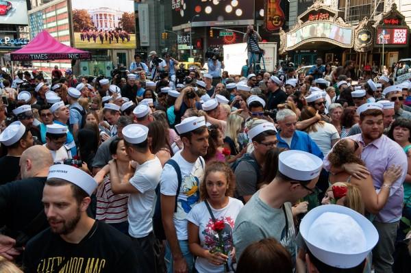 參加的男生戴著主辦單位提供的白色水手帽,女生則是手拿玫瑰花,在廣場的紀念雕像前,以照片中同樣的姿勢擁吻。(法新社)