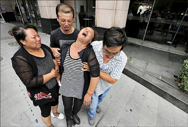 天津市政府十五日舉行新聞發布會,一群編制外消防隊員的家屬試圖衝進會場,要求官員交代失蹤隊員下落。圖為一名消防隊員母親哭倒,在其他家屬扶持下離開會場。(路透)