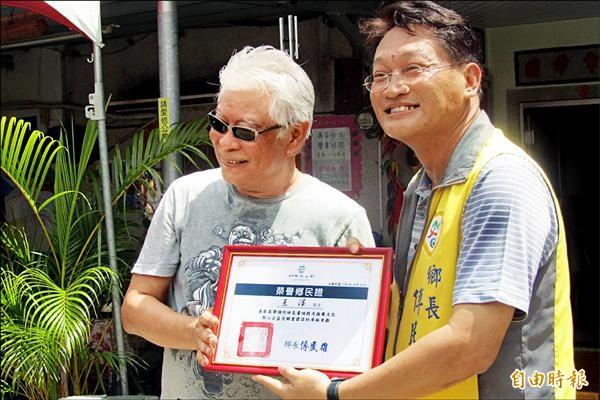 作者王澤(左)昨天特別現身,鄉長傅民雄頒發榮譽鄉民證。(記者邱芷柔攝)