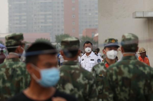 中國軍隊亦投入救災,由於爆炸區域有劇毒化學物質,可能有飄散危險,即使在收容中心附近仍戴著口罩。(法新社)